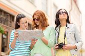 tourism, travel, leisure, holidays and friendship concept - teenage girls with map and camera outdoo