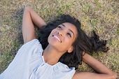 Casual pretty woman lying on the grass on a sunny day in the countryside