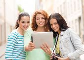 tourism, travel, leisure, holidays and friendship concept - smiling teenage girls with witch tablet