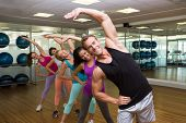 Fitness class led by handsome instructor at the gym