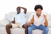 Nervous sports fans sitting on the couch with beers on white background