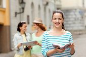 tourism, travel, leisure, holidays and friendship concept - smiling teenage girls with city guide, m