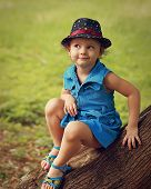 Cute Fun Kid Girl In Hat And Fashion Blue Dress Sitting On The Tree In Park