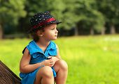 Cute Fashion Clothing Kid Girl Sitting On Tree On Green Summer Background