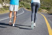 Fit couple running together down a road on a sunny day
