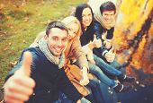 holidays, vacation, happy people concept - group of friends or couples having fun and showing thumbs