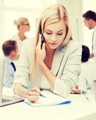 business concept - businesswoman talking on the phone and taking notes in office