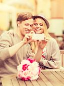 summer holidays, dating and technology concept - couple taking picture with smartphone at cafe in th