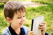 Little Boy Looking At Tablet Outdoor