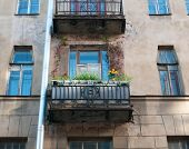 Residential Balcony Decorated With Flowers On Facade Of The Old House