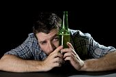 Drunk Man Wasted At Table With Beer Bottle In Hands Looking Funny
