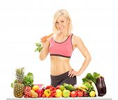 Woman holding a carrot behind a table full of fruits and vegetables isolated on white background