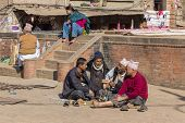 Four Unidentified Men, Seated, Smoking A Water Pipe In The Square On December 2, 2013 In Bhaktapur,