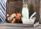 Dairy products and fresh eggs on tray, on wooden background