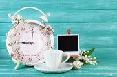 Beautiful vintage alarm clock with flowers and cup of tea on blue wooden background