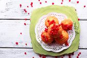 Tasty muffin with red currant berries on plate, on color wooden background