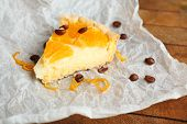 Piece of homemade orange tart on paper napkin, on color wooden background