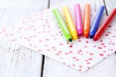Bright markers with paper on wooden table close-up