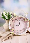 Beautiful vintage alarm clock with flowers on light background