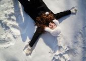 Happy teenage girl lying in the deep snow on beautiful winter day.