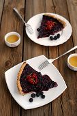 Two Pieces Of Tart With Black Currant And Blackberry Filling And Green Tea