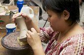 Woman cuts traditional tattoo motives decoration at kaolin, Kuching, Malaysia.