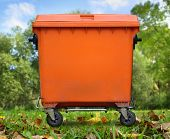 picture of garbage bin  - Single orange garbage bin closed on foliage - JPG
