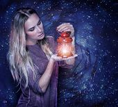 Portrait of beautiful woman with glowing lantern in hands over starry sky, magical Christmas night, fashion concept