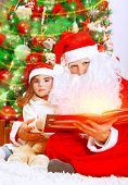 Cute little girl with Santa Claus sitting near Christmas tree and reading Magic xmas story, fairy tale, cozy festive eve at home