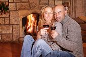 Cute couple on romantic date, beautiful woman with handsome man sitting near fireplace and drinking wine, celebrating Christmas holidays