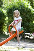 Adorable little girl having fun on a swing, against background of summer park