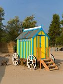 Seaside changing room bath car hut with wooden wheels in yellow and blue brightly coloured