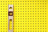 image of pegboard  - Old level hangs from a hook on yellow pegboard - JPG