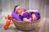Newborn baby girl in a round wicker basket