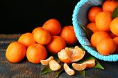 Fresh ripe mandarins in color bag, on wooden table, on dark background