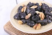 Wooden board with plate of prunes and walnuts on color wooden background