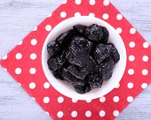 Bowl of prunes on polka-dot napkin on color wooden background