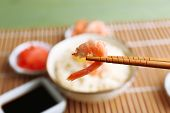 Boiled rice with shrimps and vegetables on bamboo mat background