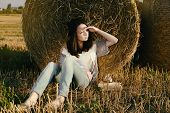 Beautiful Girl Hipster Looks Distance Against Hay Bale In Fall