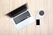 Open notebook, digital tablet, diary, smart phone and a cup of coffee on wooden background, top view
