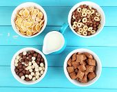 Various sweet cereals in ceramic bowls and jug with milk on color wooden background