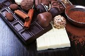 Bars of chocolate, sweet candies and strainer with cocoa on the dark wooden smooth background