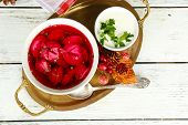 Traditional polish clear red borscht with dumplings in bowl on tray and Christmas decorations on wooden background