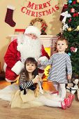 Santa Claus with two little cute girls near  fireplace and Christmas tree at home