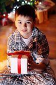 Little boy sitting near fireplace in room