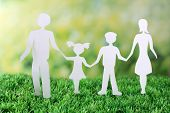 Paper family on green grass on light background