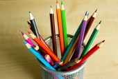 Colorful pencils in metal holder on wooden background