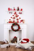 Fireplace with Christmas decoration and cushions on wooden floor and white wall background