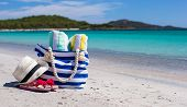 Beach bag, straw hat, flip flops and towel on white tropical beach