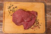 raw beef on wooden cutting board with  pepper